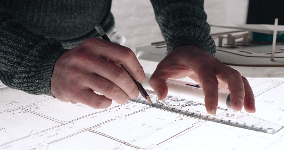 Close up of Man's hands drawing lines on the Large Format Paper at Modern Office. Architect using Ruler and Pencil to make Blueprints on the Paper. Having very Responsible Job. Great work. Royalty-Free Stock Footage #1059571172