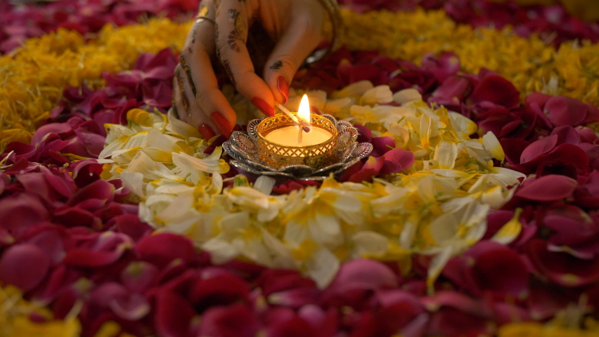 Closeup shot of an Indian female's hand decorating floral rangoli with a Diya. Hand of a woman lighting up a beautiful oil lamp placed in the center of a colorful rangoli - Diwali festival