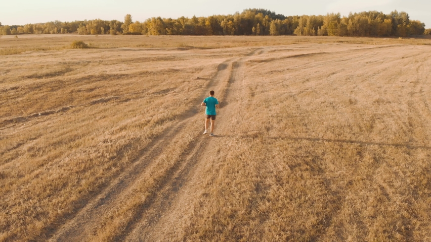 Aerial view running man in sunset time. Outdoor cross-country running. Athletic young man is running in the nature during golden sunset. Healthy lifestyle. | Shutterstock HD Video #1059574745
