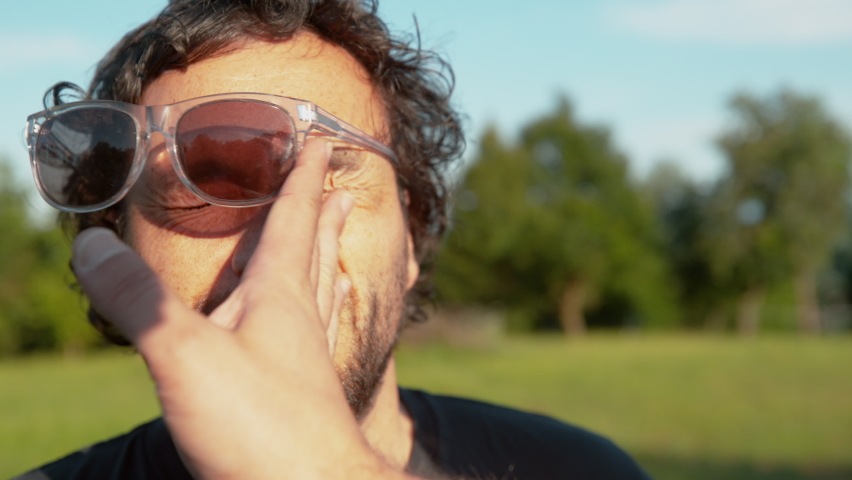 SLOW MOTION, CLOSE UP, DOF: Curly-haired man's sunglasses fly off his face after getting slapped by unknown person. Funny shot of hand slapping the cheek of a bearded guy standing with his eyes closed