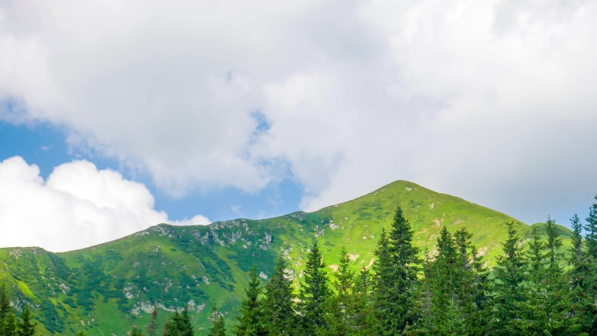 White rain clouds fly over mountain range with green grass at blue sky background at the foot of the mountains is pine forest landscape timelapse motion | Shutterstock HD Video #1059579986