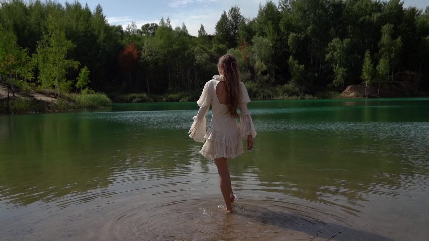 One young woman in a white dress goes and wets her feet on a wild forest lake in summer. | Shutterstock HD Video #1059580358