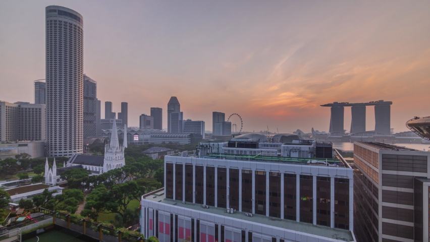 Sunrise over Singapore skyline with St. Andrew's Cathedral aerial night timelapse. It is an Anglican cathedral in Singapore, the country's largest cathedral. Skyscrapers on a background Royalty-Free Stock Footage #1059581903