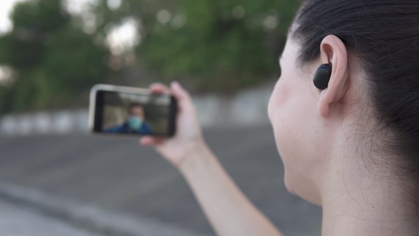 The girl speaks on a video chat with a friend on the street | Shutterstock HD Video #1059582392
