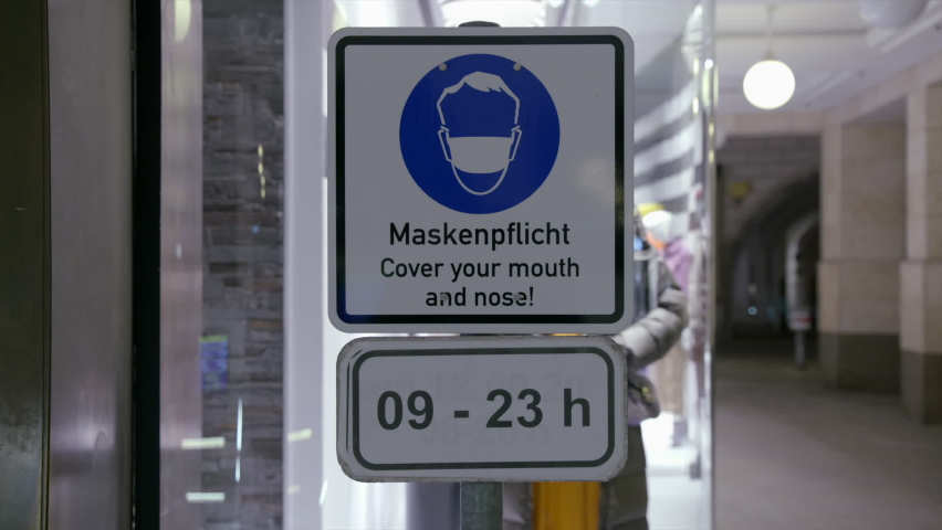 A sign for the mask requirement in the inner city at night 8 in Munich Bavaria Germany 09.24.2020 | Shutterstock HD Video #1059582482