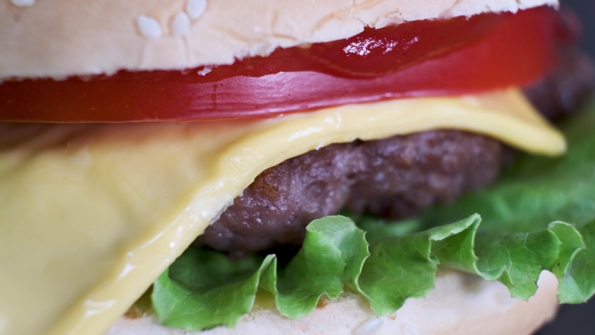 Rotating burger with beef, cheese, tomato, salad leaf in white bun, close-up. | Shutterstock HD Video #1059582497