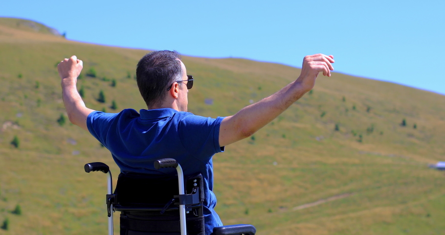 Optimistic handicapped man sitting on wheelchair raising his hands and admiring nature on the mountain. Travel and freedom concept. Hand held shot at 4k | Shutterstock HD Video #1059583322