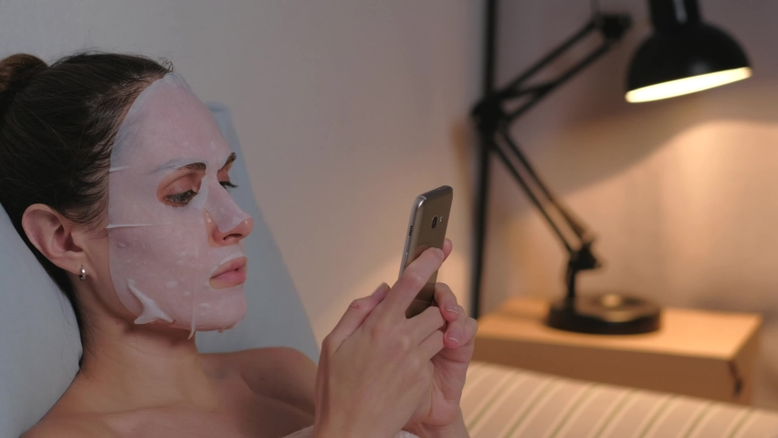 Brunette woman with face mask use smartphone in soft bed in the evening at home. Close up. Skin care concept. Slider or dolly shot. | Shutterstock HD Video #1059584750