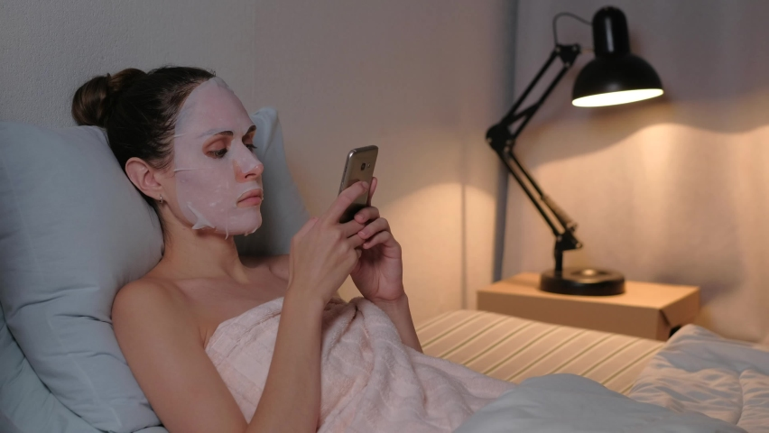 Cute female with face mask use smartphone relaxing in soft bed in the evening at home. Skin care concept. Slider or dolly shot. | Shutterstock HD Video #1059584753