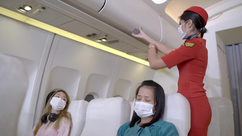 Passenger sitting airplane when woman cabin crew with face mask checking airplane storage before take off. Concept new traveling for healthcare protocols and prevent virus pandemic. | Shutterstock HD Video #1059586064