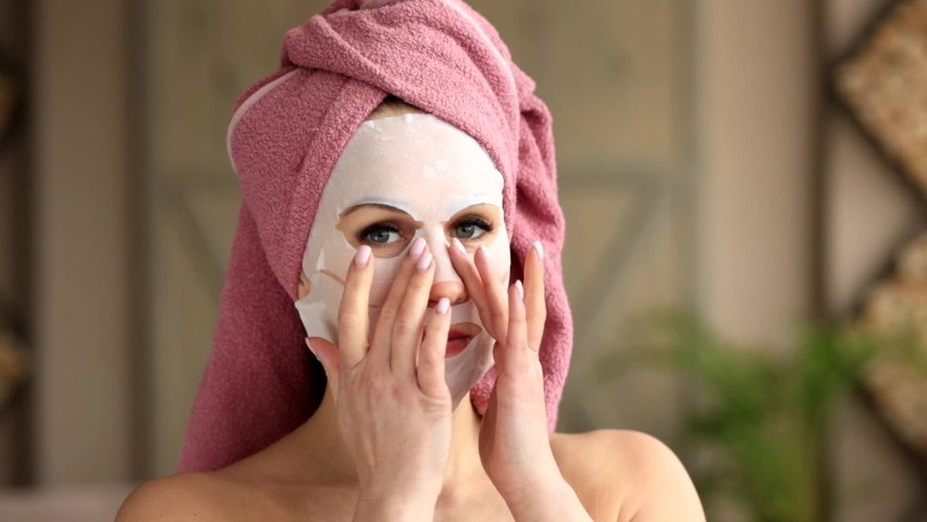 A happy girl with a pink towel on her head,blue eyes and bare shoulders smoothes a fabric cosmetic mask on her face with her fingers.Spa at home | Shutterstock HD Video #1059586358