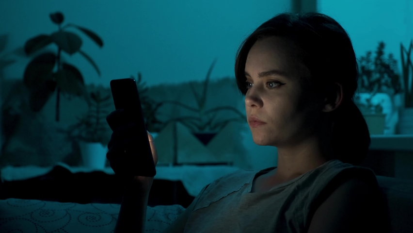 Woman scrolling mobile phone at night. Beautiful girl reading on smart phone sitting on a couch at home