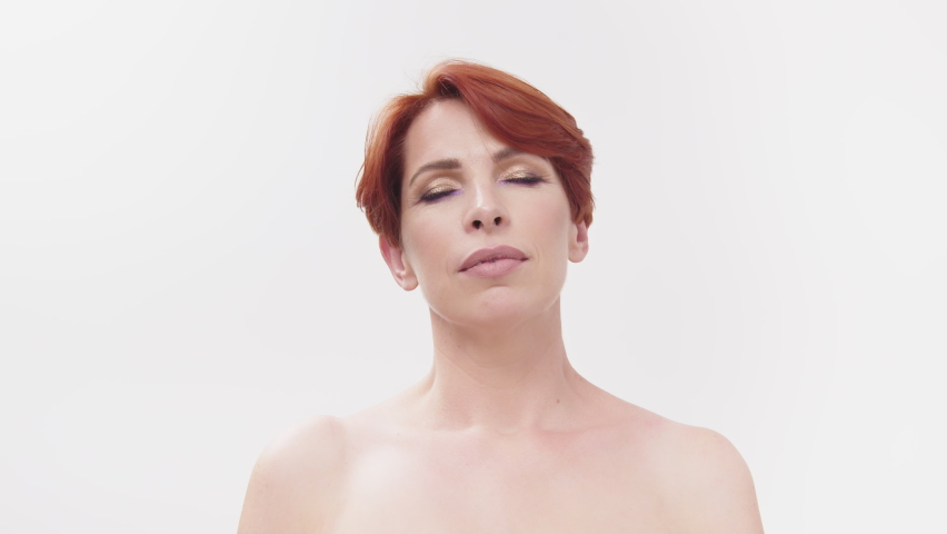 Beauty head shot. Nude redhead woman in 40s with closed eyes isolated on white | Shutterstock HD Video #1059588545