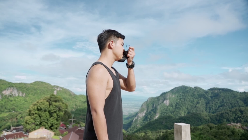 Asian young male remove face mask and feel the wind blow fresh air, man standing on top of the mountain stretch, corona covid-19 pandemic, air pollution, feeling fresh air without mask, new normal