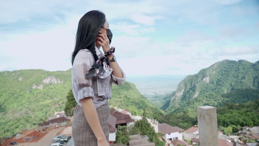Young Asian light skin woman  take off face mask standing on top of the mountain stretch out arms to feel wind blow, fresh pure oxygen, corona covid-19 pandemic, feeling fresh air, new normal