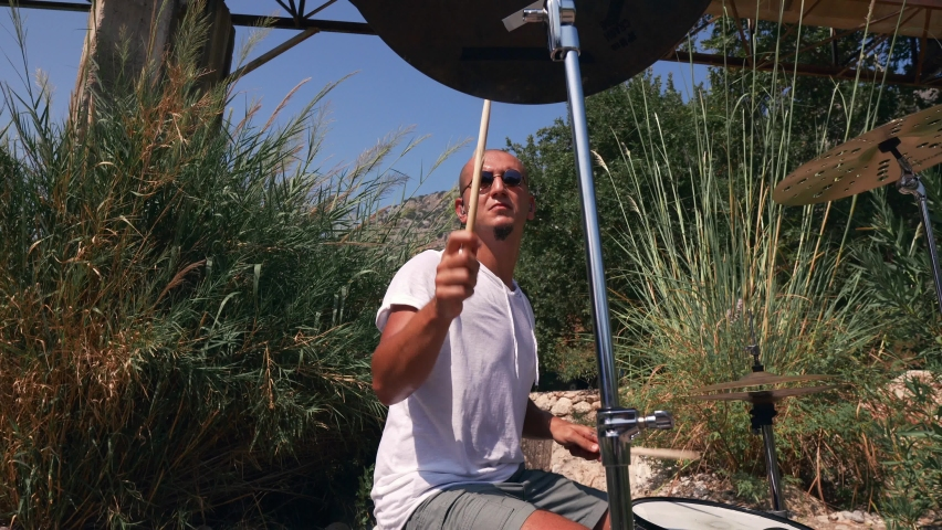 The guy plays drums coolly in the nature Expressive performance 4K Low Angle  | Shutterstock HD Video #1059591749
