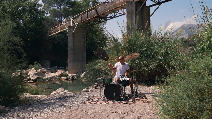 The guy plays drums coolly in the nature Expressive performance 4K Full Shot | Shutterstock HD Video #1059591752