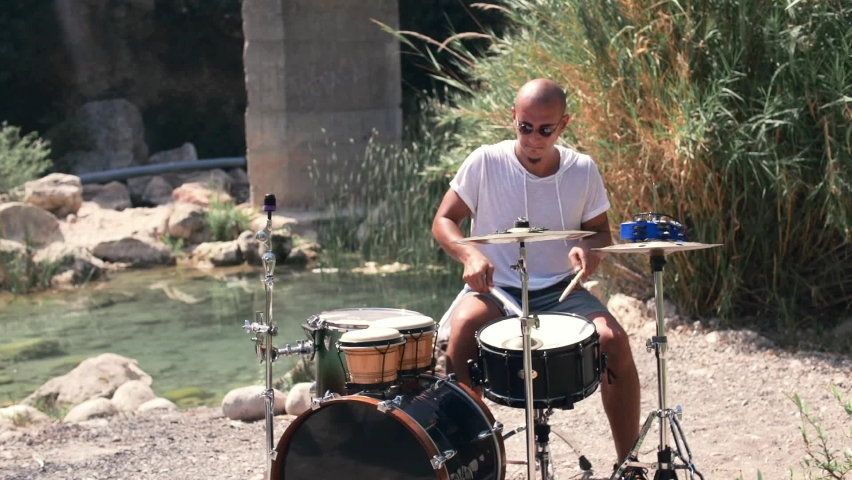 The guy plays drums coolly in the nature Expressive performance Medium shot | Shutterstock HD Video #1059591776