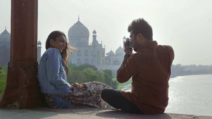 A happy and young romantic couple is sitting outdoors against Taj mahal and girlfriend is posing for boyfriend who is clicking pictures using a camera. Cheerful male and female enjoying time together