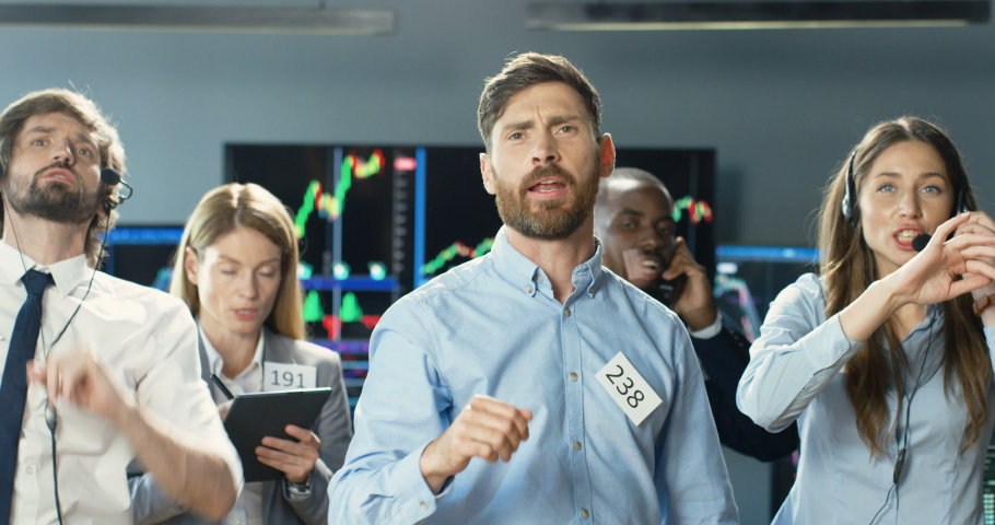 Caucasian young man broker selling or buying on stock market with group of mixed-races colleagues. Male trader putting bets and rates at exchange. Mixed-races co-workers of trading screaming. Royalty-Free Stock Footage #1059598853