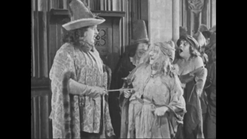 CIRCA 1923 - In this silent movie adaptation of the Hunchback of Notre Dame, old beggar women mock an aristocratic guard.
