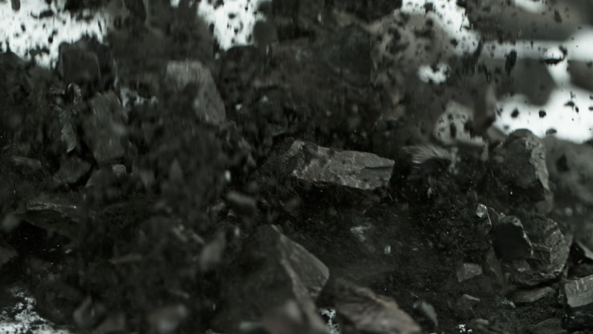 Super Slow Motion Shot of Coal and Black Powder Falling on White Background at 1000 fps.