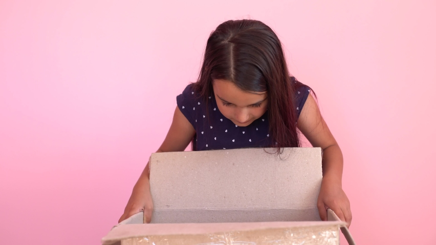A girl looks in the box, is surprised and happy to receive a surprise. The child opened a box with a gift. | Shutterstock HD Video #1059622775