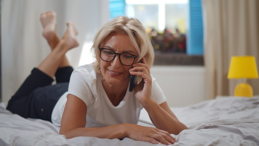 Senior caucasian woman lying on bed making phone call in bedroom at home. Portrait beautiful of smiling mature female talking on smartphone relaxing on bed in morning