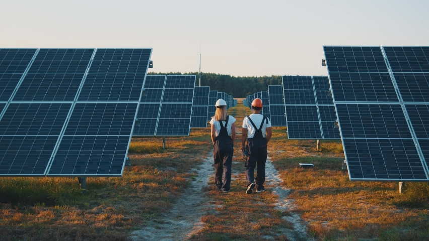 Business team of industrial technicians walking through solar park outside. Construction of concentrated solar power plant. Renewable energy. Ecology. Royalty-Free Stock Footage #1059627164
