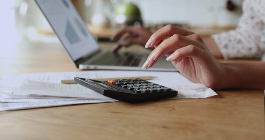 Close up woman accountant working using calculator and laptop, graphs statistics on device screen. Make payments on-line through secure bank system, analyze company charges calculate expenses concept Royalty-Free Stock Footage #1059629990