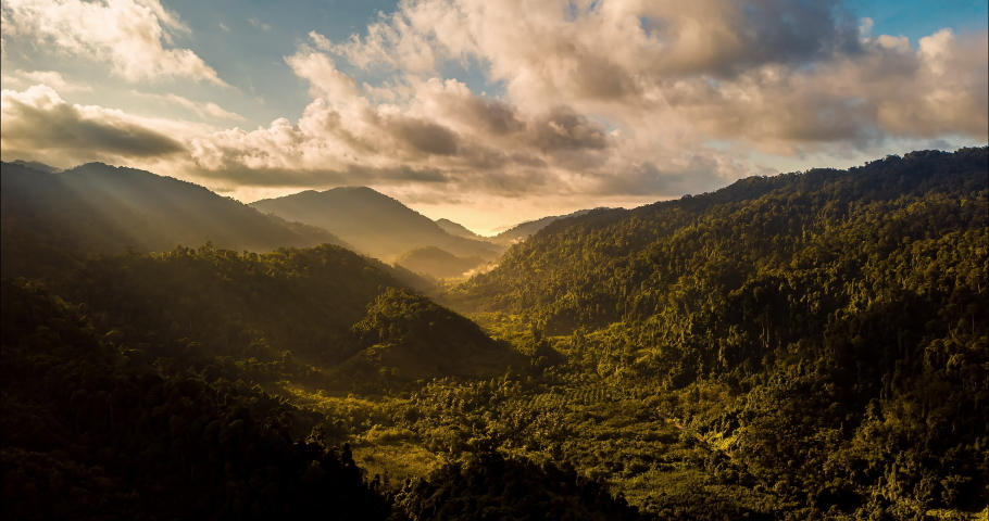 Aerial drone hyperlapse timelapse of beautiful tropical valley between mountains. The first rays of the rising sun break through the clouds and clouds. The last rays of the sunset hit the tree crowns.   Shutterstock HD Video #1059635909