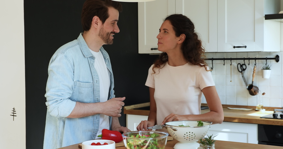 Couple in love preparing vegetarian food in home kitchen, husband feed beloved wife with leaf of lettuce talking enjoy date cooking together. Romantic relationship, healthy dish and lifestyle concept