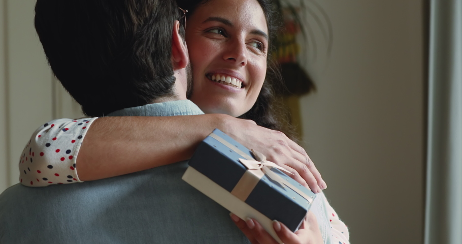 Rear view husband hugs wife makes surprise. Close up face happy female cuddles beloved man hold giftbox express gratitude for gift at 8-march International Women Day, life events celebrations concept Royalty-Free Stock Footage #1059636452