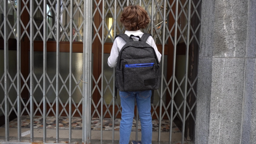 child mask and backpack goes back to school after lockdown due to Covid-19 Coronavirus global pandemic - arrives to the school closed Royalty-Free Stock Footage #1059641516
