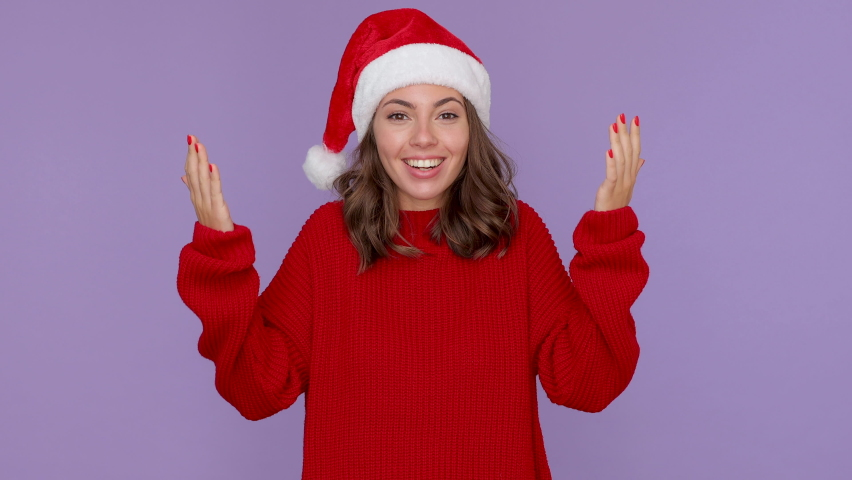 Shocked surprised amazed young woman in red knitted cozy sweater Santa Christmas hat say omg wow put hands on head isolated on purple violet background studio. Happy New Year celebration merry holiday | Shutterstock HD Video #1059642875