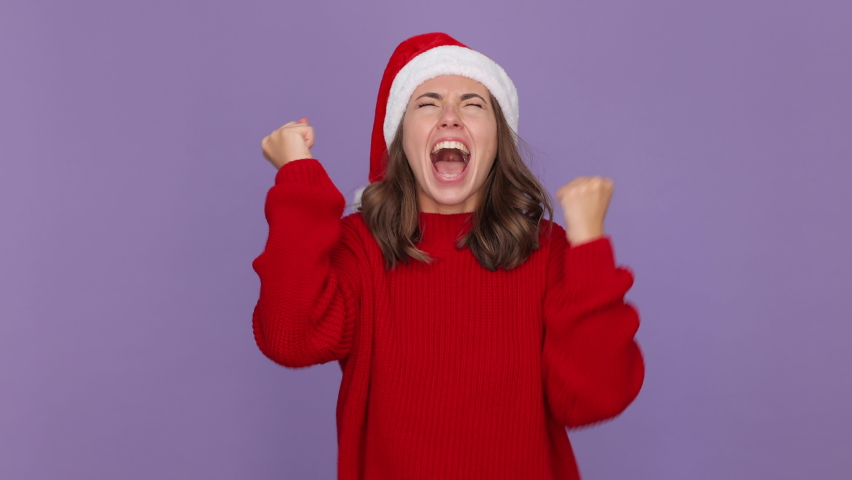 Young woman in red knitted cozy sweater Santa Christmas hat keeping fingers crossed making wish doing winner gesture say Yes isolated on purple violet background studio. Happy New Year holiday concept | Shutterstock HD Video #1059642881
