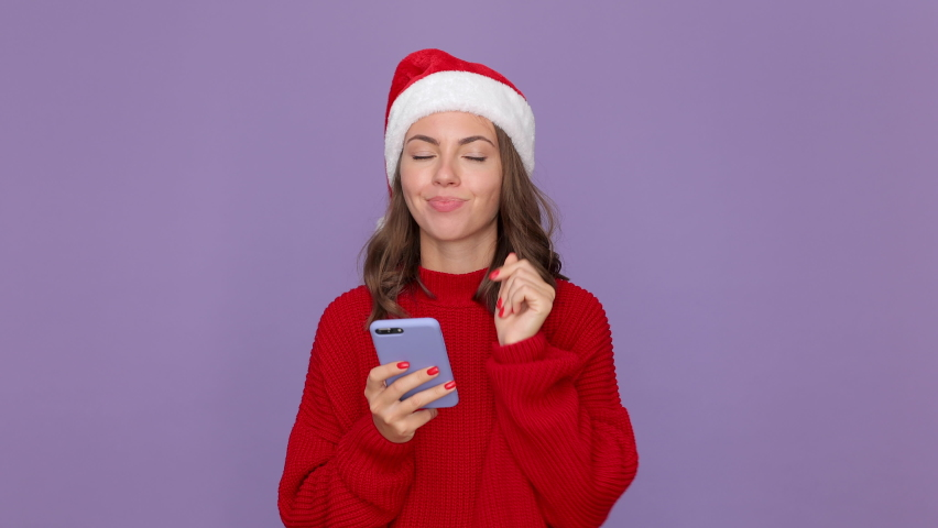 Young woman 20s in red knitted cozy sweater Santa Christmas hat holding using mobile cell phone typing sms isolated on purple violet background studio. Happy New Year celebration merry holiday concept | Shutterstock HD Video #1059642932