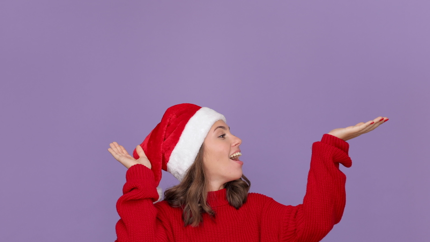 Cute young woman 20s in red knitted cozy sweater Santa Christmas hat raised hands up like catch falling snowflakes isolated on violet background studio Happy New Year celebration merry holiday concept | Shutterstock HD Video #1059642956