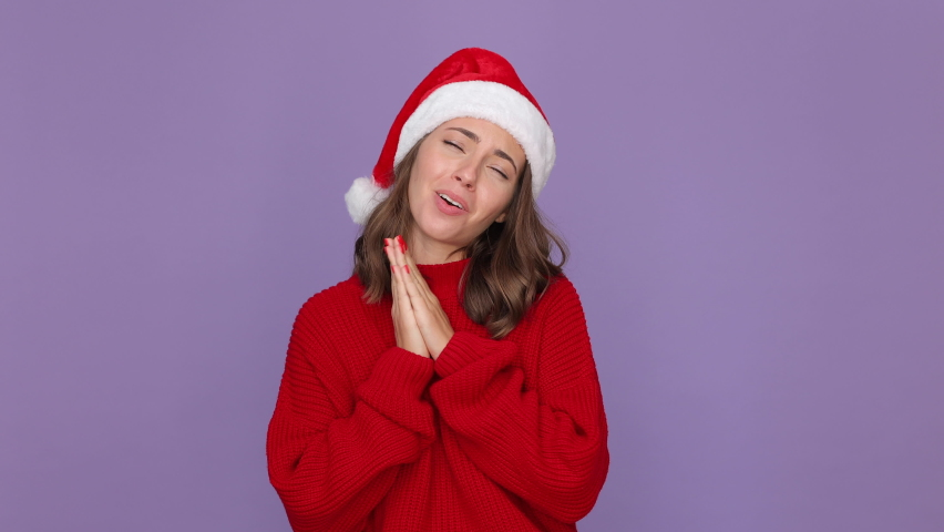 Cute young woman 20s in red knitted cozy sweater Santa Christmas hat say ask who me oh it so sweet put pull hands on chest isolated on violet background studio. Happy New Year merry holiday concept | Shutterstock HD Video #1059642977