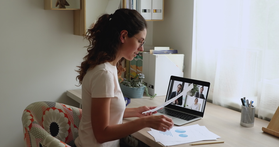 Businesswoman sit at desk hold papers discuss documents with charts financial graphs talk to work team use video conference app and pc. Videocall easy convenient method solve business issues concept Royalty-Free Stock Footage #1059643784