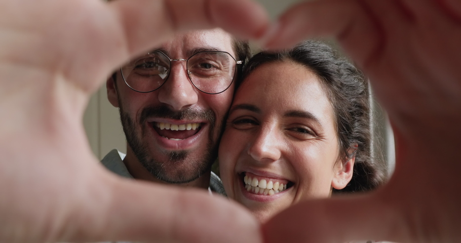 Close up portrait happy couple faces looking through joined fingers making heart shape. St Valentines Day celebration, romantic relationships, just married spouses, sincere feelings and love concept Royalty-Free Stock Footage #1059643868