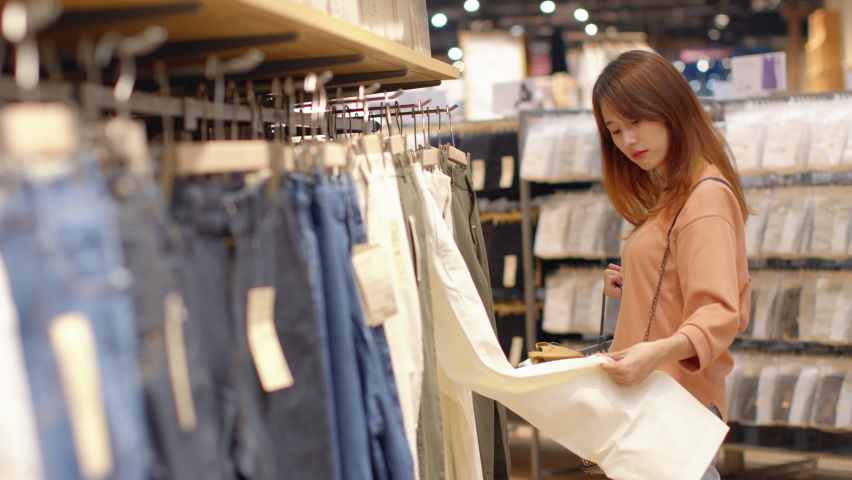 Pretty Young Asian woman Choosing clothes in a clothing store. Female Customer in casual clothing Choosing clothes from rack, shelf in department store. buying for a christmas gift or holiday gift.