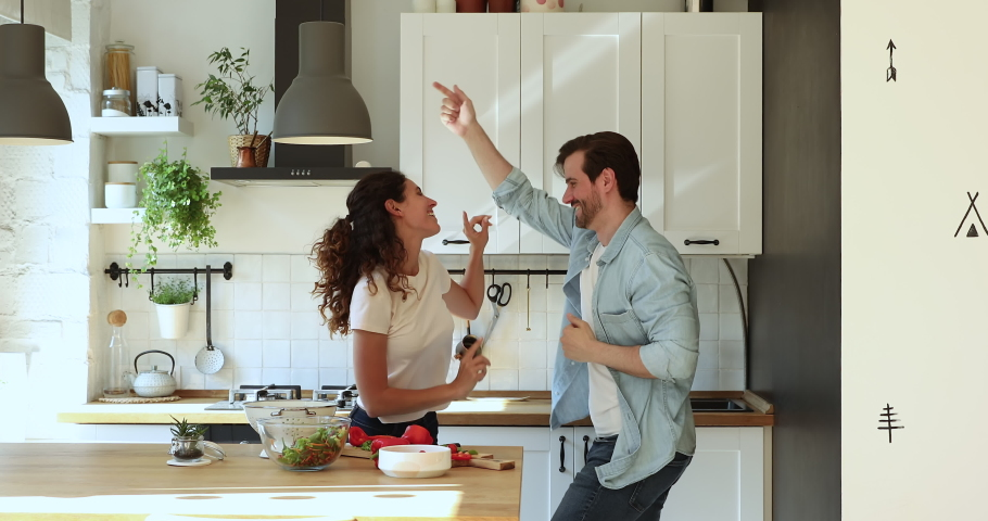 Happy couple in love holds hands dance in domestic kitchen. Spend together weekend active time, excited homeowners and celebration of first dinner at new home enjoy of romantic date, lifestyle concept Royalty-Free Stock Footage #1059650063