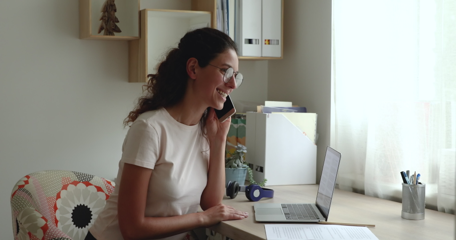 Woman in glasses writes notes while talk on phone with colleague sit at desk in front of laptop working remotely do telecommute job from home using mobile connection, solve business distantly concept