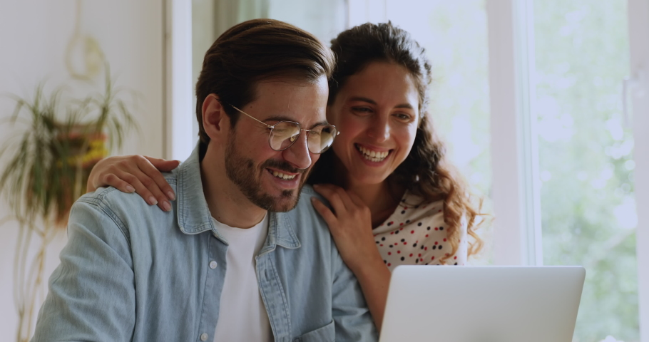 Happy couple buying on internet using laptop spend time at home. Easy on-line payment for tickets, makes purchase distantly through modern technology, booking hotel, pleasant costs remotely concept Royalty-Free Stock Footage #1059650105