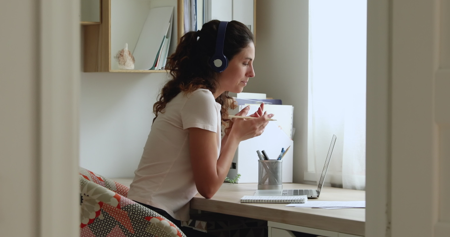 Woman sit at desk wear headphones gain new knowledge using video call laptop and services of e-teacher. Advanced training, learning foreign language remotely, modern tech and internet connection usage
