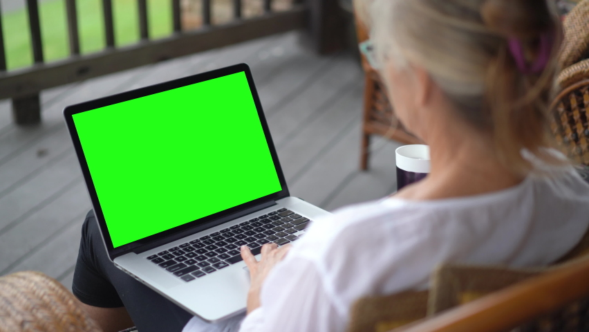 Over shoulder closeup view of woman daughter wfh work from home video calling with green screen and talking someone on the laptop screen. Family video call concept.
