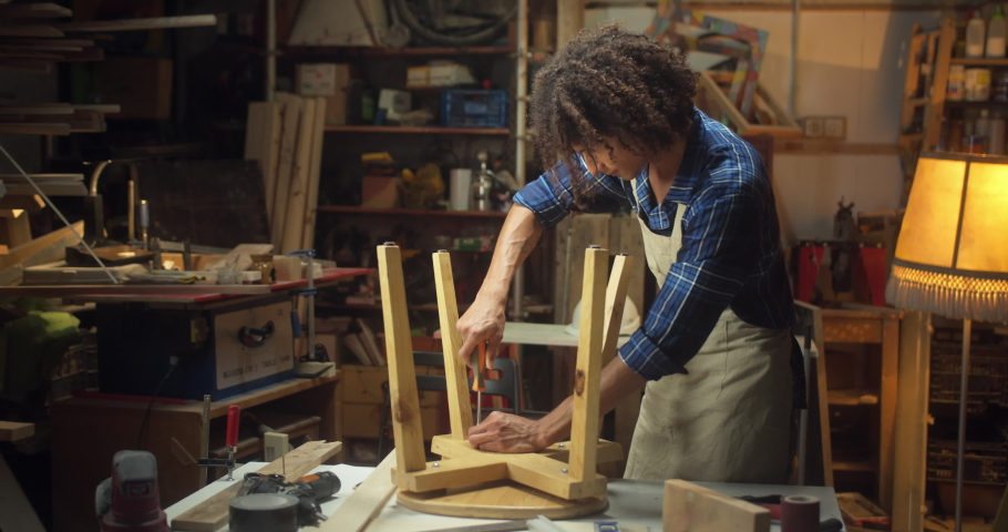 Curly joiner male master furniture assembler twists screw screwdriver chair in workshop, professional carpenter in apron and shirt working on project workbench engaged in assembling furniture   Shutterstock HD Video #1059656327