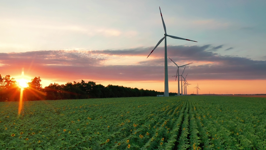 Aerial view of wind turbines standing in sunset. Aerial View of a Farm With Wind Turbines. Generating Clean Renewable Energy. bright orange sunset wind park drone. Alternative energy  Royalty-Free Stock Footage #1059656711