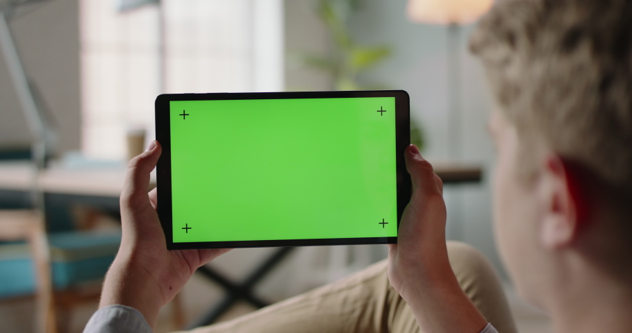 Close up shot of guy using a tablet computer with green mockup screen. Student during online lesson or work conference on self-isolation 4k footage | Shutterstock HD Video #1059657053